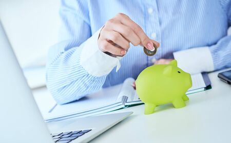 Womans hand putting money coin in green piggy bank close-up in office background. Growing business, pension and insurance savings concept. Фото со стока