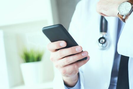 Male doctor in white coat is using a modern smartphone device with touch screen. Doctor hands with mobile phone.
