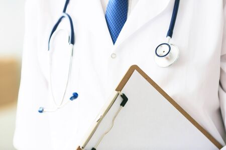 Close-up of clipboard with blank paper in medical doctor hand. Young male therapist is preparing for an interview with a patient.