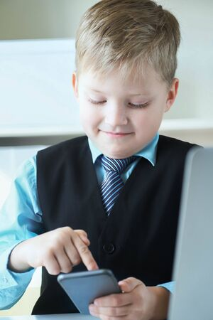 Smart little boy in suit working on laptop and touching the phone screen emotionally. Banque d'images - 129467746