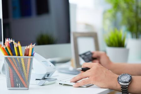 Mans hands holding a credit card and using computer keyboard for online shopping or payment.