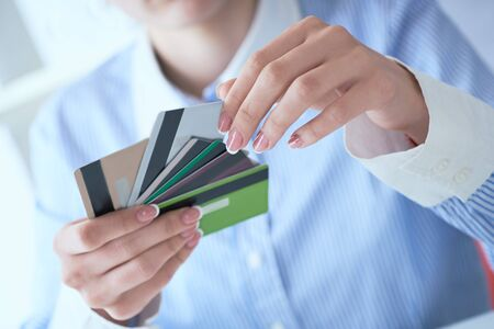 Woman hand holding various credit cards and making choice with another hand close-up. Stock fotó