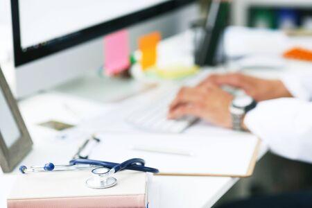 Médecin de sexe masculin travaillant avec un ordinateur portable. Presse-papiers, stylo et stéthoscope sur le bureau en gros plan de l'hôpital. Médecin de sexe masculin travaillant avec un ordinateur en arrière-plan.