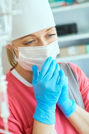 Young woman doctor anesthesiologist dressed in pink gown, mask and hat prepares solution for anesthesia in the operating room.