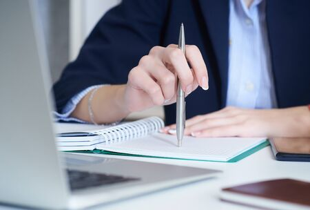 Young businesswoman holdinп pen in hand while reading infщrmation at laptop screen. Female hands holding a pen and making notes close up.