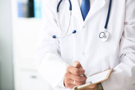 Male doctor in white coat on duty writes information with pen in clipboard close up. Selective focus. Health and medical concept.