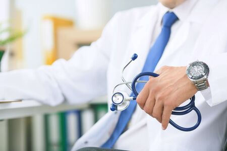 Close-up of a young male doctor in a white coat sitting at a table in a medical office and holding a stethoscope in his hand. Male doctor listens to the patient sitting in the armchair. Stock Photo