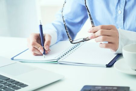 Spectacles placed in businesswoman hand close-up. Young woman writing in notepad. Vision concept