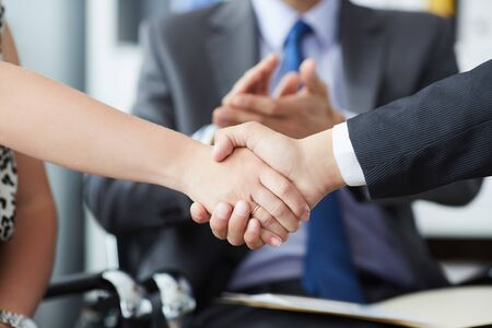 Business people shaking hands, finishing up a meeting. Male and female hands in handshake closeup with male coallegue in background. Stock Photo