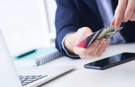 Businesswoman with many different credit cards in hands close-up. Cashless payments, anti-fraud and financial security, entering client discount program number, filling personal information concept.