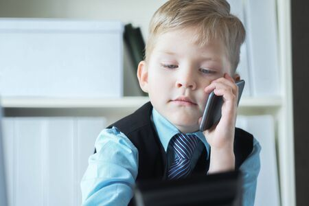 Young confident executive businessman boss boy in office talks on the phone sitting at the desk with laptop. Stock Photo