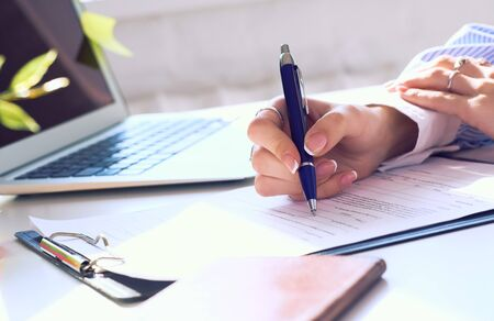 Businesswoman sitting at office desk signing a contract or making notes. Stock Photo