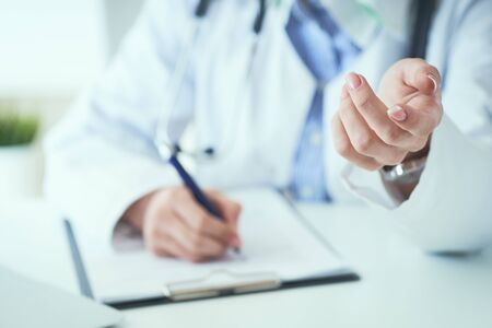 Female doctor explaining patient symptoms or asking a question as they discuss together in a consultation. Doctor held out his hand to the patient close-up.