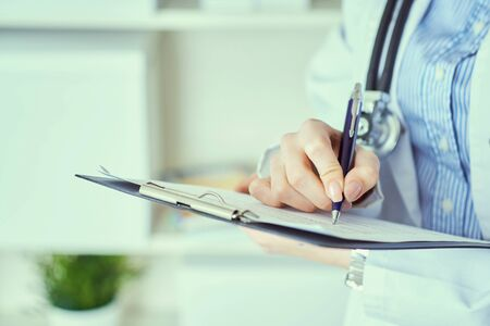 Female doctor hand hold silver pen filling patient history list at clipboard pad. Panacea and life save, prescribing treatment.