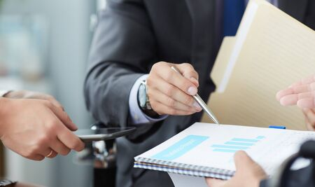 Businessman and woman discussing on stock market charts in office. Men in a suit hold a clipboard with financial charts.