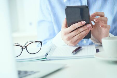 Close up of hand of businesswoman using smartphone at office. Business, technology and people concept. Stock Photo