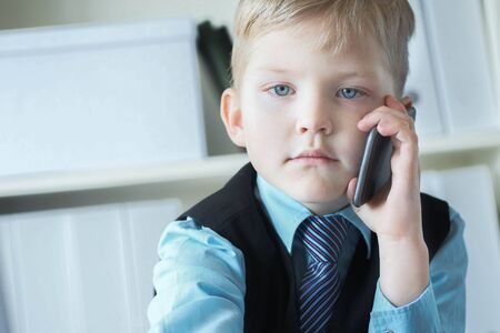 Little confident executive businessman boss boy in office talks on the phone sitting at the desk with laptop.
