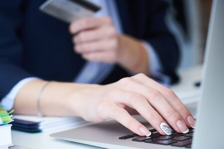 Businesswoman inputting her password and login to carry out online banking operation on laptop pc in the office. Anti-fraud and financial security, entering client discount program number, filling personal information concept Stock Photo
