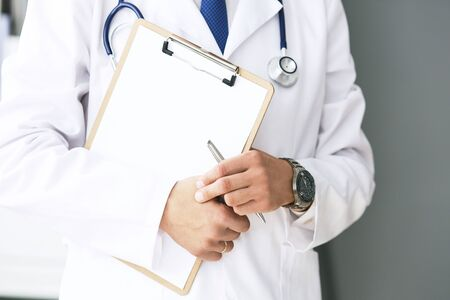 Close-up of clipboard with blank paper in medical doctor hand. Male doctor listens to the patient holding a clipboard with documents for hospitalization. Stock Photo