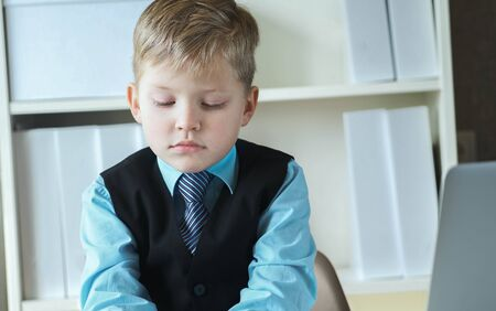 Concentrated small boy in suit thinking about money and budget increasing ways. Little financial director.