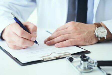 Środkowa część męskiego lekarza piszącego receptę pacjentowi przy stole roboczym. Panaceum i życie ratują, przepisując leczenie.