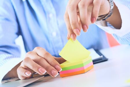 Accountant woman tears off color sticker, close up.