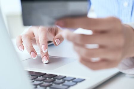 Rear view of male hands holding credit card typing numbers on computer keyboard while sitting at home at the wooden table, soft focus, flare sun light, cross process image