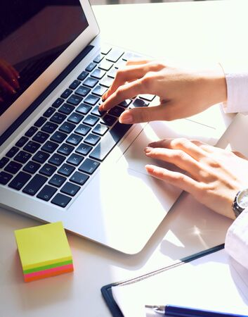 Female hands working on laptop on light background Stock Photo