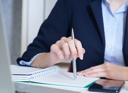 Young businesswoman holding pen in hand while reading information at laptop screen. Female hands holding a pen and making notes close up. Stock Photo