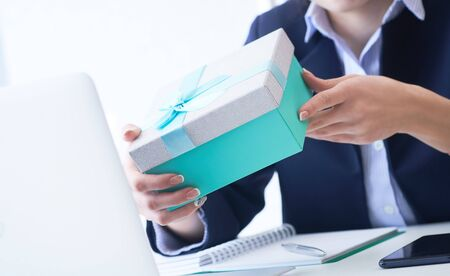 Christmas, any holiday. Office employee received a gift from her colleagues. Closeup woman hands holds blue gift box on office background. Stock Photo