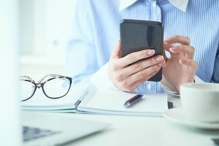 Mid section of businesswoman using smartphone at office. Business, technology and people concept.