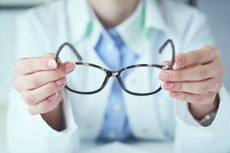 Female optician hands giving new glasses to customer for testing and trying close-up.