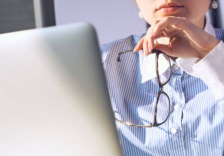 Thoughtful female office manager with spectacles in hand near the chin looking at laptop screen sitting at working place.