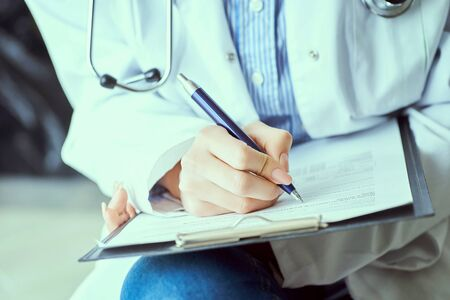 Female doctor hand hold silver pen filling patient history list at clipboard pad.