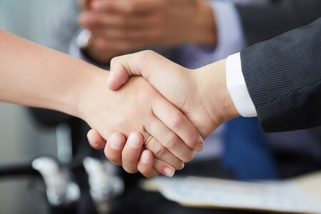 Business people shaking hands, finishing up a meeting. Male and female hands in handshake closeup. Stock Photo