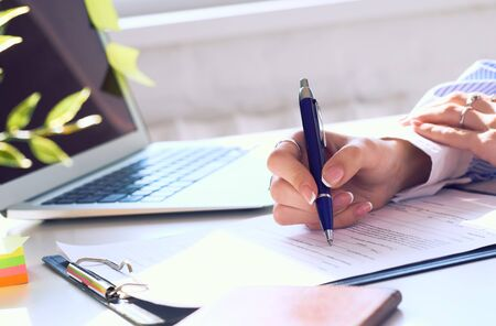 Businesswoman sitting at office desk signing a contract or making notes closeup. Stock Photo