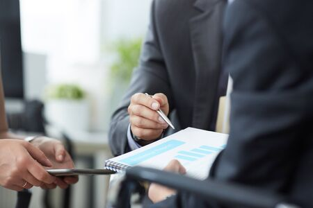 Men in a suit hold a clipboard with financial charts in office. Stock Photo