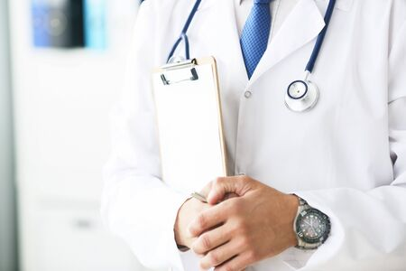 Close-up of clipboard with blank paper in medical doctor hand.