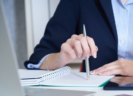 Female hands holding a pen and making notes close up. Woman writing letter, list, plan, making notes, doing homework. Student studying. Education, self development and perfection concept Stock Photo