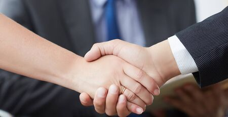 Business people shaking hands, finishing up a meeting. Male and female hands in handshake closeup with male colleague in background. Stock Photo