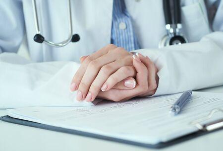 Jonge vrouwelijke arts luistert aandachtig naar klachten van patiënten, handen op elkaar geklemd. Artsen en patiënten zitten en praten met de patiënt over medicatie. Stockfoto