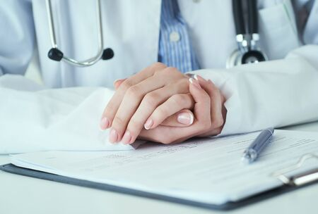 Young woman doctor listens attentively to patient complaints, hands clasped one on top of the other. Doctors and patients sit and talk to the patient about medication. Stock fotó