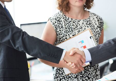 Business people in suits shaking hands, finishing up a meeting. Male hands in handshake closeup with female colleague in background.