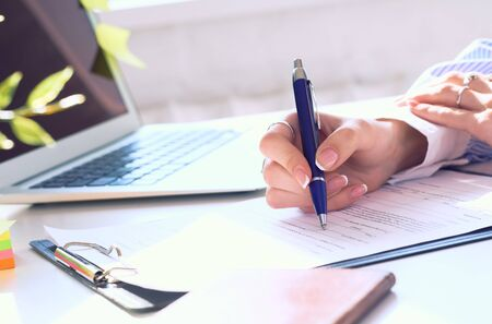 Businesswoman sitting at office desk signing a contract or making notes. Banque d'images