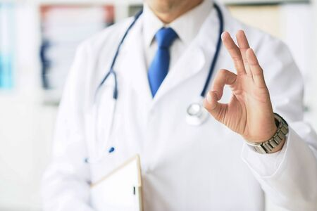 Close up of male doctor in white coat showing ok hand sign.