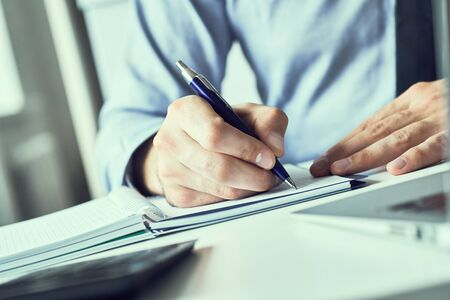 Businessman signing a document, taking notes, completing a questionnaire or writing correspondence. Close up view of man hand and the clipboard. Banco de Imagens