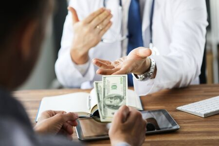 Patient giving money to medical doctor in hospital setting. Doctor gladly accepts a bribe from the patient actively gesticulating. Banco de Imagens