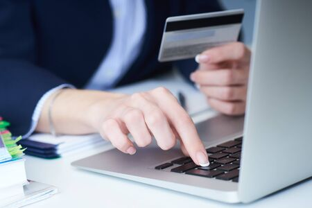 Businesswoman inputting her password and login to carry out online banking operation on laptop pc in the office. Womans hand holding credit card close-up.
