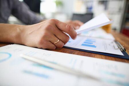 Nahaufnahme eines männlichen Mitarbeiters, der während des Büromeetings Papierhandout-Material liest, Mann, der den Papierkrambericht beim Briefing analysiert. Standard-Bild