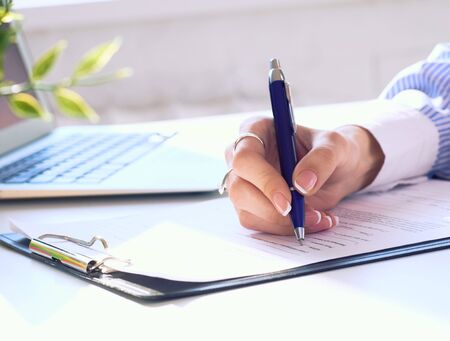 Businesswoman sitting at office desk signing a contract or making notes. Stok Fotoğraf